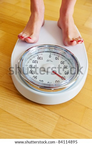 Turn the feet of a woman standing on bathroom scales to