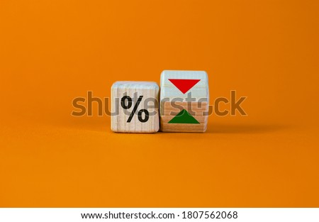 Turned a cube and changed the direction of an arrow symbolizing that the interest rates are going down or vice versa. Beautiful orange background. Business concept. Copy space. Foto stock ©
