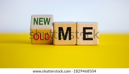 Turned a cube and changed the expression 'old me' to 'new me'. Beautiful yellow table, white background. Business and lifestyle concept, copy space. Stok fotoğraf ©