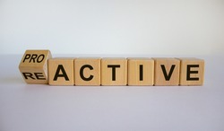 Turned a cube and changed the word reactive to proactive. Business concept. Beautiful white background, copy space.