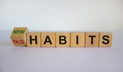 Turned cube and changed the expression 'old habits' to 'new habits'. Beautiful white background. Concept. Copy space.