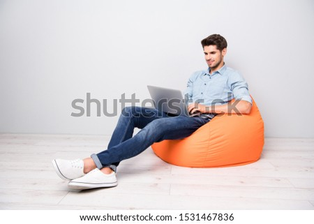 Turned full length body size photo of attractive handsome cheerful enjoying man chatting with his friends coworking isolated over grey color background