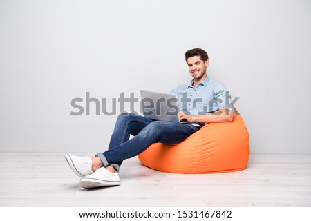 Turned full length body size photo of cheerful toothy handsome attractive man smiling beaming enjoying finishing his project isolated over grey color background