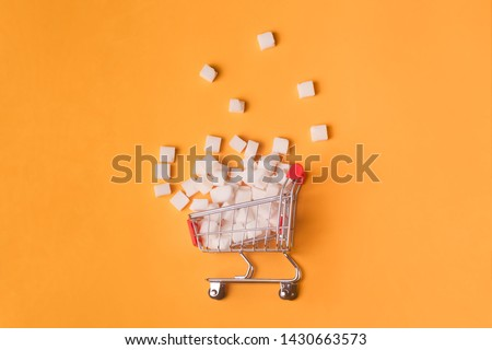Turned pushcart with pile of white sugar cubes on orange background, sugar rejection concept