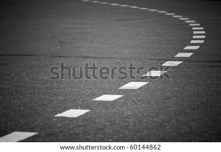 Turning asphalt road with marking lines. Close up photo