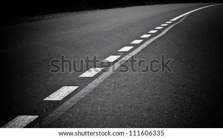 Turning dark asphalt road with marking lines. Close up photo