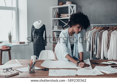 Turning ideas into clothing. Beautiful young African woman working on sketches while standing in her studio near the clothes hanging on the racks - Shutterstock ID 589230362