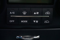 Turning on the air conditioning of a car on the climate control panel.
