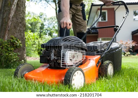 Turning on the lawn mower by gardener #218201704