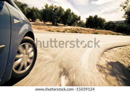 Turning wheel at high speed in the countryside. - stock photo