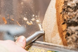 Turning wooden bowls on a lathe. The close up view of spinning the lathe machine. Man with a chisel and shavings flying off.