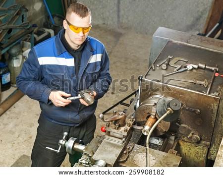 Turning work. Worker measuring  turning part ny micro meter