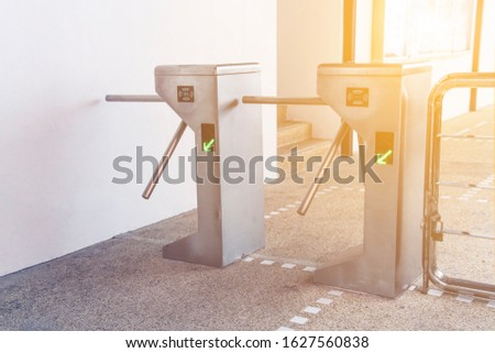 Turnstiles, focus on the left turnstile. Checkpoint. Automatic access control. Access system to enter building. Automatic electronic entrance. Entrance gate with turnstile.