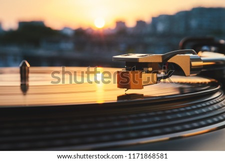 Turntable vinyl record player on the background of a sunset over the lights city. Sound technology for DJ to mix & play music. Black vinyl record. Vintage vinyl record player. Needle on a vinyl record #1171868581