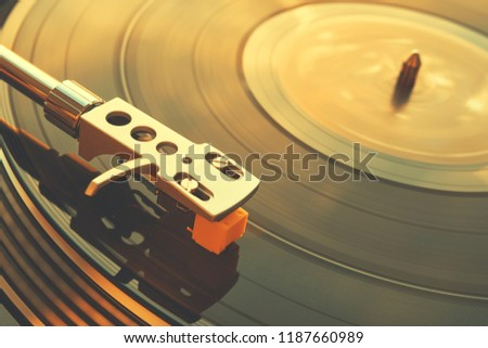 Turntable vinyl record player on the background of a sunset over the lights city. Sound technology for DJ to mix & play music. Black vinyl record. Vintage vinyl record player. Needle on a vinyl record #1187660989