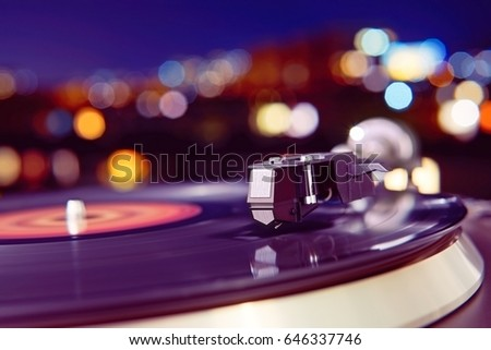 Turntable vinyl record player on the background of a sunset over the lights city. Sound technology for DJ to mix & play music. Black vinyl record. Vintage vinyl record player. Needle on a vinyl record #646337746