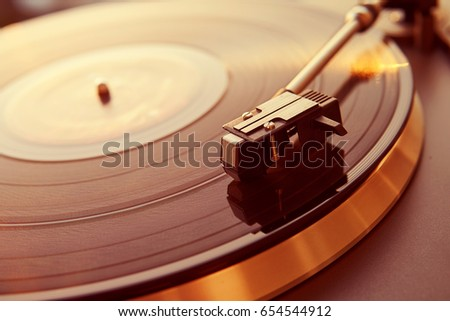 Turntable vinyl record player on the background of a sunset over the lights city. Sound technology for DJ to mix & play music. Black vinyl record. Vintage vinyl record player. Needle on a vinyl record #654544912
