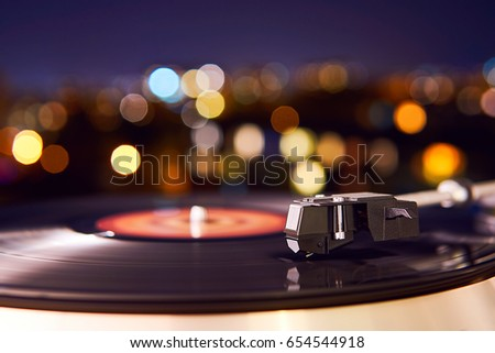 Turntable vinyl record player on the background of a sunset over the lights city. Sound technology for DJ to mix & play music. Black vinyl record. Vintage vinyl record player. Needle on a vinyl record #654544918