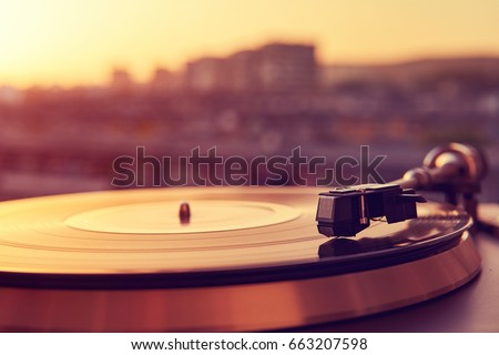 Turntable vinyl record player on the background of a sunset over the lights city. Sound technology for DJ to mix & play music. Black vinyl record. Vintage vinyl record player. Needle on a vinyl record #663207598