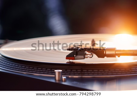 Turntable vinyl record player on the background of a sunset over the lights city. Sound technology for DJ to mix & play music. Black vinyl record. Vintage vinyl record player. Needle on a vinyl record #794298799