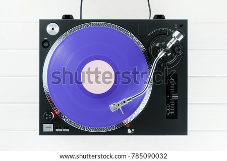 Turntable vinyl record player on the background of their white wooden boards. Sound technology for DJ to mix & play music. Needle on a vinyl record. Purple vinyl record           #785090032