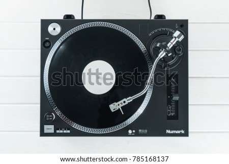 Turntable vinyl record player on the background of their white wooden boards. Sound technology for DJ to mix & play music. Needle on a vinyl record. Black vinyl record    #785168137