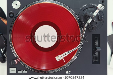 Turntable vinyl record player on the background white wooden boards. Sound technology for DJ to mix & play music. Needle on a vinyl record. Red vinyl record                                             #1090567226