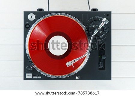 Turntable vinyl record player on the background white wooden boards. Sound technology for DJ to mix & play music. Needle on a vinyl record. Red vinyl record