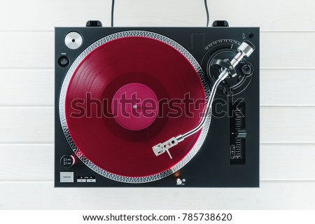 Turntable vinyl record player on the background white wooden boards. Sound technology for DJ to mix & play music. Needle on a vinyl record. Red vinyl record #785738620