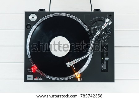 Turntable vinyl record player on the background white wooden boards. Sound technology for DJ to mix & play music. Needle on a vinyl record. Black vinyl record