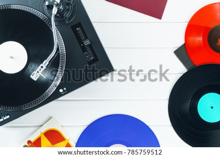 Turntable vinyl record player on the background white wooden boards. Sound technology for DJ to mix & play music. Needle on a vinyl record. Red vinyl record. Black vinyl record    #785759512