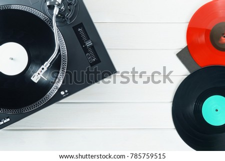 Turntable vinyl record player on the background white wooden boards. Sound technology for DJ to mix & play music. Needle on a vinyl record. Red vinyl record. Black vinyl record    #785759515