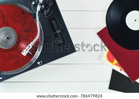 Turntable vinyl record player on the background white wooden boards. Sound technology for DJ to mix & play music. Needle on a vinyl record. Red vinyl record. Black vinyl record                         #786479824