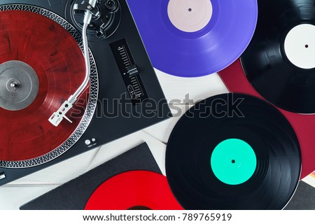 Turntable vinyl record player on the background white wooden boards. Sound technology for DJ to mix & play music. Needle on a vinyl record. Red vinyl record. Black vinyl record                         #789765919