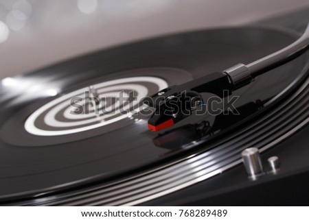 Turntable vinyl record player. Sound technology for DJ to mix & play music. Vintage vinyl record player on a background decorations for a party, bright disco lights. Needle on a vinyl record           #768289489