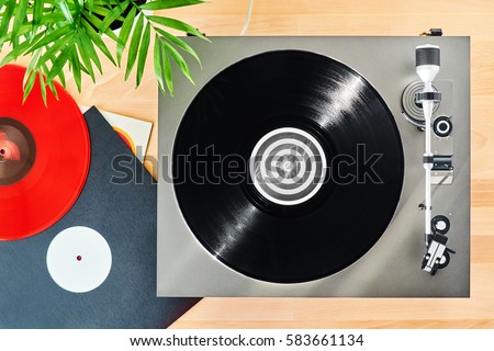 Turntable vinyl record player to listen on a wooden table. Red plate. Included gramophone and torque plate closeup. Sound technology for DJ to mix & play music. Black vinyl record #583661134