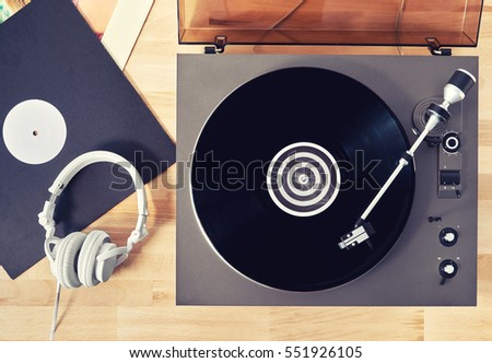 Turntable vinyl record player  with vinyl records and headphones on a wooden table. Sound technology for DJ to mix & play music. Black vinyl record. Vintage vinyl record player #551926105