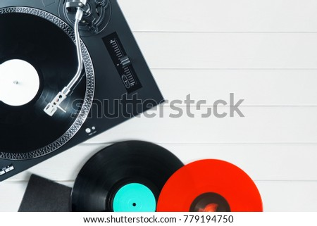Turntable vinyl record player  with vinyl records and headphones on a wooden table. Sound technology for DJ to mix & play music. Black vinyl record. Vinyl record player     #779194750