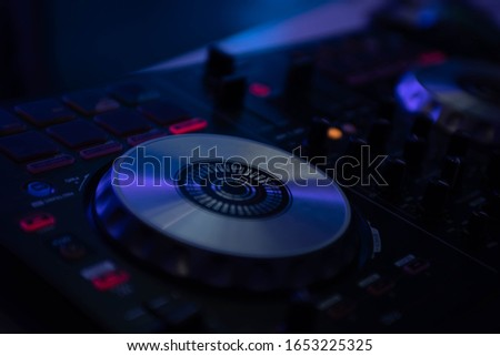 turntables of the DJ music console in the light of club lighting