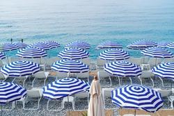turquiose water of cote dAzur over striped beach umbrellas