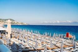 turquiose water of cote dAzur with striped beach umbrellas