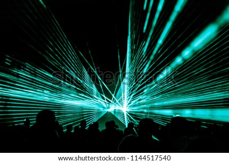 Turquois laser show nightlife club stage with party people crowd. Luxury entertainment with audience silhouettes in nightclub event, festival or New Year's Eve. Beams and rays shining colorful lights