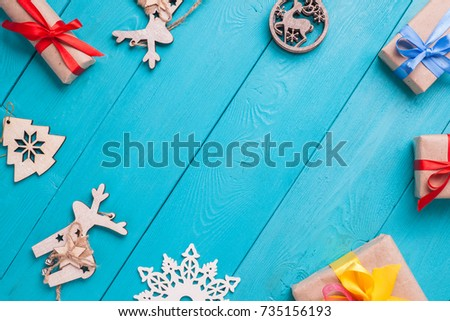 Turquoise background for Christmas cards. Background for Christmas wishes. Blue wooden boards. Holiday toys and gifts arranged in a circle - Shutterstock ID 735156193