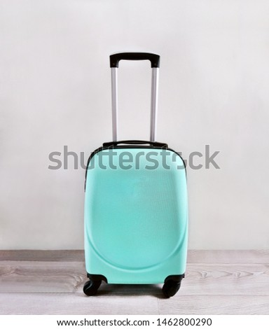Turquoise, blue plastic suitcase with handle on a gray background for travel, vacation, travel, low-cost flights. Template for advertising, social networks, web page #1462800290