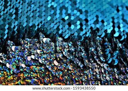 turquoise blue sequins shining with multicolored shining sequins flowing the opposite way