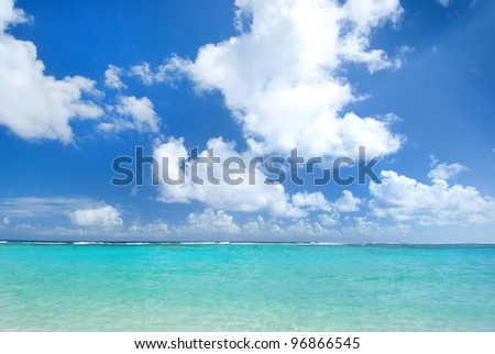 Turquoise caribbean waters with blue cloudy sky overhead