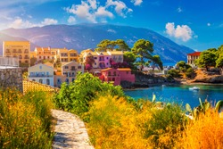 Turquoise colored bay in Mediterranean sea with beautiful colorful houses in Assos village in Kefalonia, Greece. Town of Assos with colorful houses on the mediterranean sea, Greece.