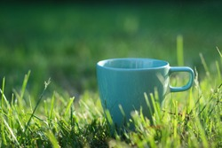 Turquoise Cup with a hot steaming drink in nature. Cup with tea or coffee on green grass with sunlight. A blue cupon blurred green natural background.