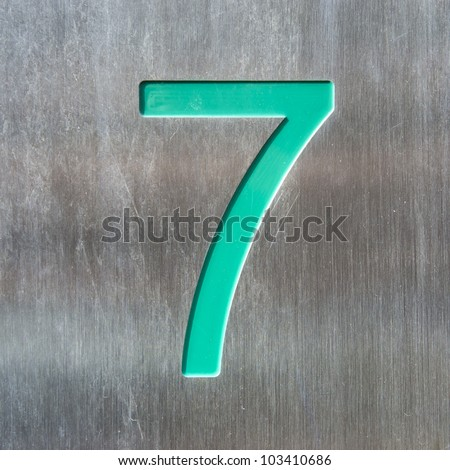turquoise house number seven engraved in a stainless steel plate,.