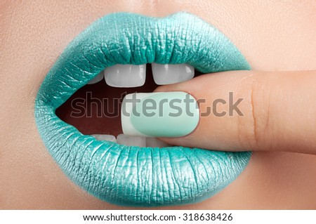 Turquoise lip gloss and a beautiful nails.
